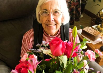 resident smiling holding bouquet of flowers